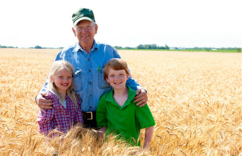 Farmer in field with his hands on two young children